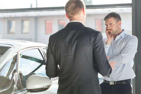 car retailer: Photo of mature client in car showroom