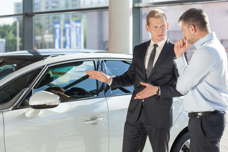 Autohändler, der dem reifen Mann Fahrzeug zeigt Standard-Bild