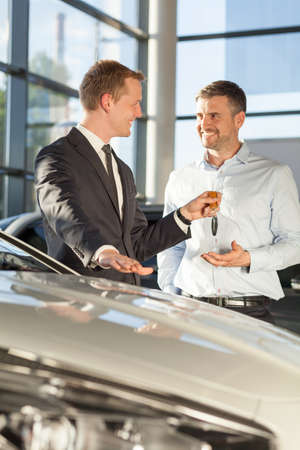 new driver: Car dealer giving client keys of his new car
