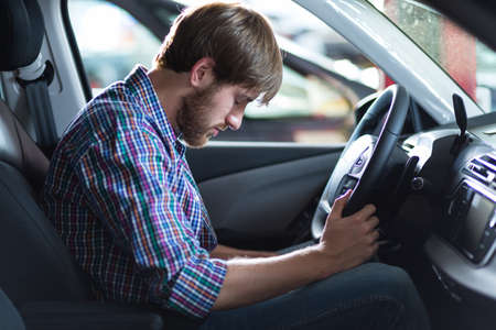 worried businessman: Young troubled driver having problem with car