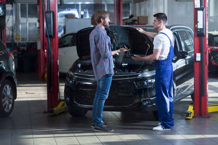 automotive repair: Young automotive technician talking with male client