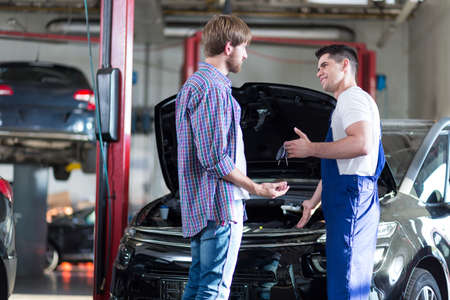 automobile workshop: Mechanic giving client keys to his repaired car