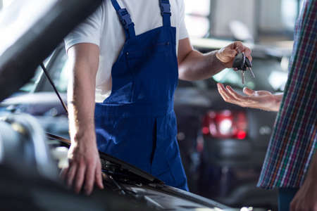 Auto mechanics hands giving a car keys Stock Photo
