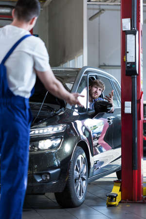 repaired: Angry male client sitting in repaired car Stock Photo