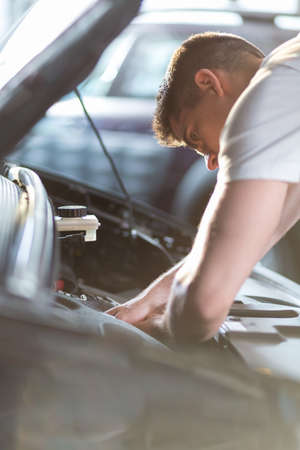 service: Automobile mechanic repairing a car in service station