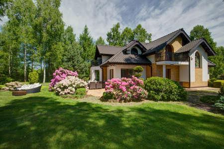 casa de campo: Exterior de la casa unifamiliar con jardín belleza
