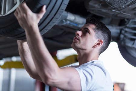 automotive technician: Automotive technician changing a wheel in the garage