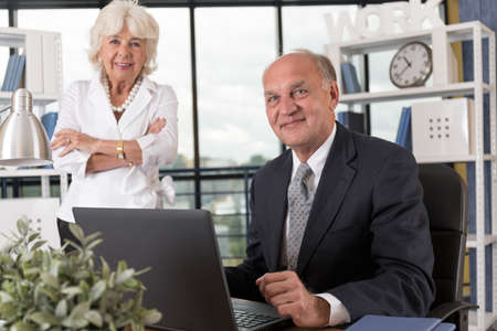 businesswoman suit: Portrait of elderly business couple in bureau