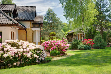 summer house: Beauty spring-flowering shrubs in designed garden Stock Photo
