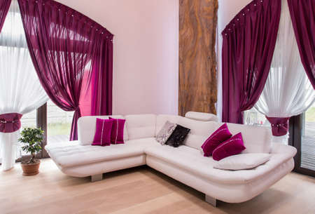 White comfortable corner sofa and rose cushions