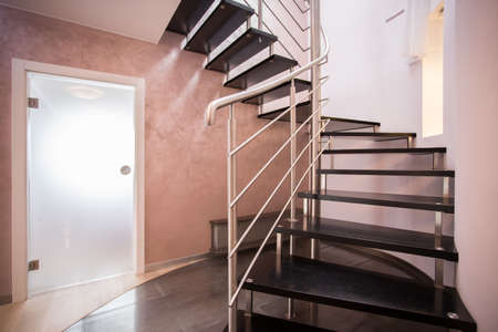 anteroom: Wooden spiral stairs in luxury modern house Stock Photo
