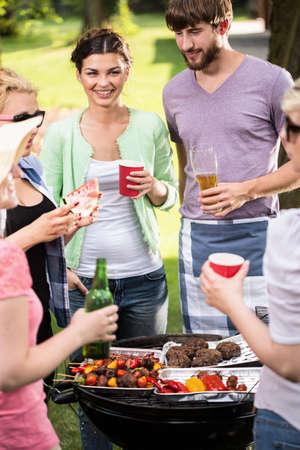 chorizos asados: Amigos felices haciendo barbacoa en el horario de verano Foto de archivo