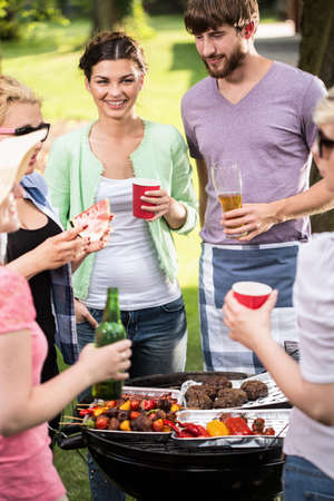 relax garden: Happy friends doing barbecue at summer time Stock Photo