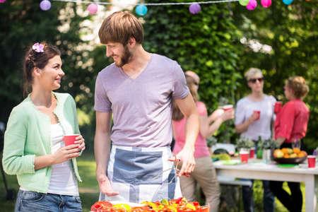 Jonge paar doen grill partij in de tuin Stockfoto