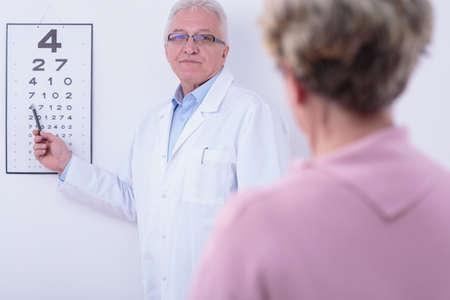 Oftalmólogo Mayor control de los ojos de su paciente de edad avanzada Foto de archivo - 42293202