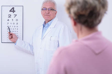 Older ophthalmologist checking his older patient's sight