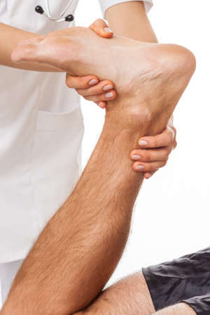treat acupressure: Doctors hands diagnosing patient with painful foot Stock Photo