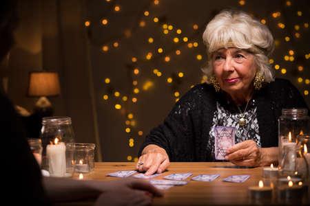 fortune telling: Photo of smiling elder female telling someones fortune Stock Photo