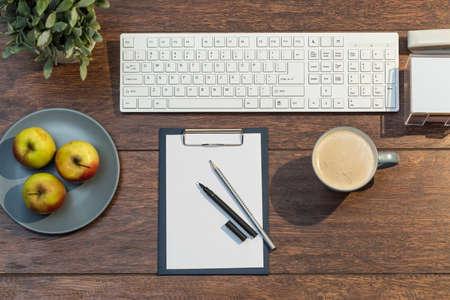 papeles oficina: Escritorio con la taza de caf� y un plato de manzanas