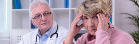 persona enferma: Una m�s vieja mujer preocupada con dolor de cabeza en la oficina del m�dico