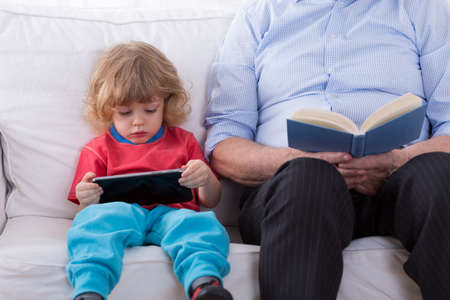 books new books: Little smart boy learning how to use tablet Stock Photo