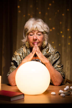 Image of fortune teller using magic ball during seance Stock Photo