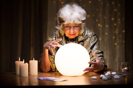 mystique: Photo of woman foretelling future from crystal ball Stock Photo