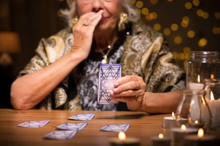 spiritualism: Close up of aged fortune teller reading tarot card meaning