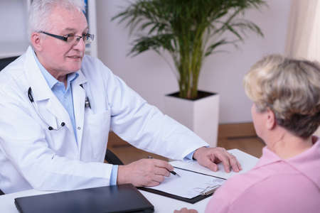 medical history: Aged experienced physician filling older patients medical history