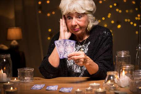 spirit medium: Picture of shocked female fortune teller reading cards