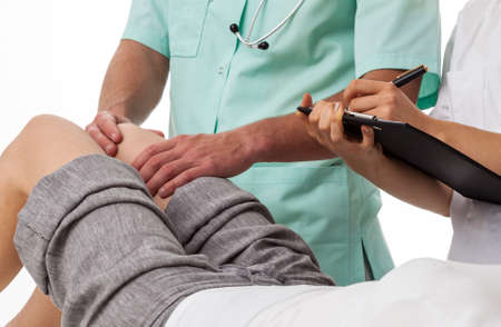 diagnosing: Orthopedist diagnosing patients knee and other doctor writing Stock Photo