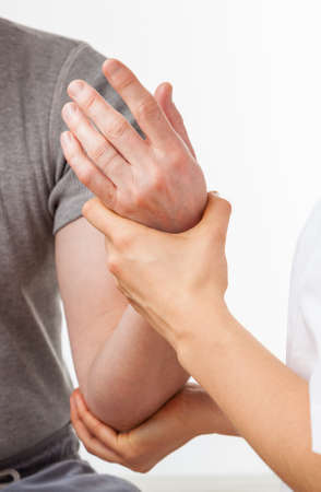 female elbow: Close-up of physiotherapist exercising elbow after injury Stock Photo