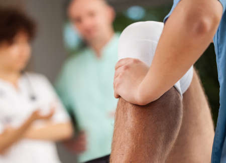knee: Physiotherapist training with patient and doctors in background