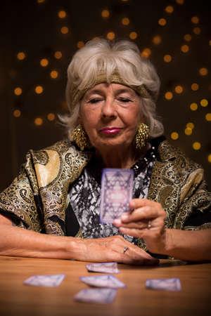 foretelling: Photo of elder female foretelling future from tarot cards Stock Photo