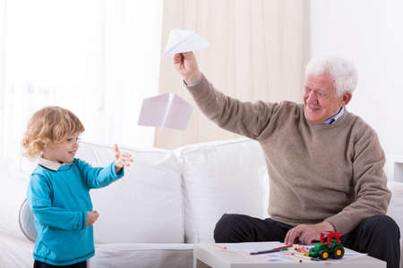 letting: Happy little kid letting with grandfather paper airplane