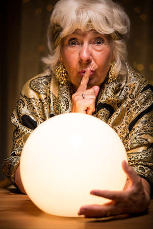 Photo of terrified female medium holding magic ball during seance