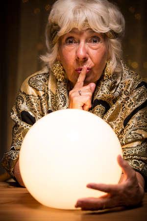 seance: Photo of terrified female medium holding magic ball during seance