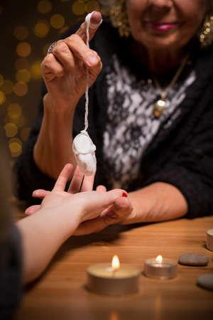 pendulum: Close up of female fortune teller using pendulum during seance