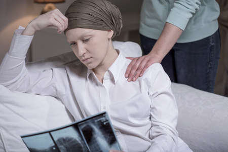Broken down young cancer woman sitting at home with friend