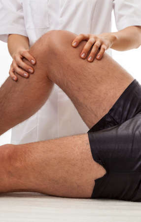 diagnosing: Orthopedists hands diagnosing patient with painful knee Stock Photo