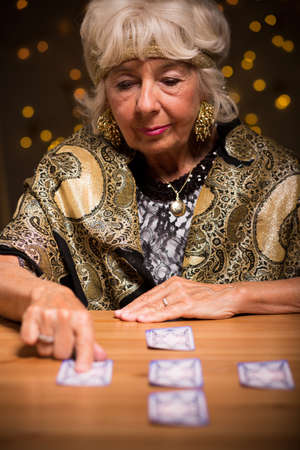 telling: Image of kind mature tarot reader telling someones fortune