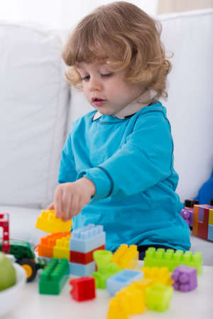 blond boy: Little cute boy setting tower from colorful blocks Stock Photo