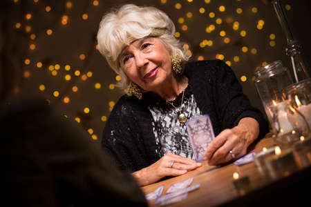 Image of smiling elderly female seer during seance Stock Photo