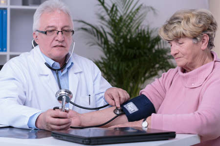 office visit: Professional doctor measuring older patients blood pressure Stock Photo