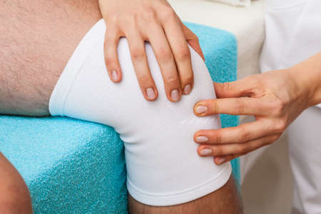 kneecap: Physiotherapist doing patellar mobilisation after knee injury Stock Photo