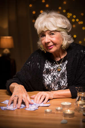 seance: Picture of smiling aged tarot reader telling fortune