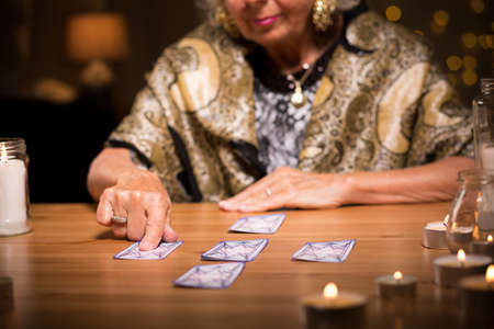 seer: Photo of elder woman predicting future from cards