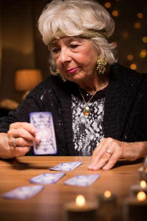 Foto van oude vrouw vertellen fortuin van kaarten