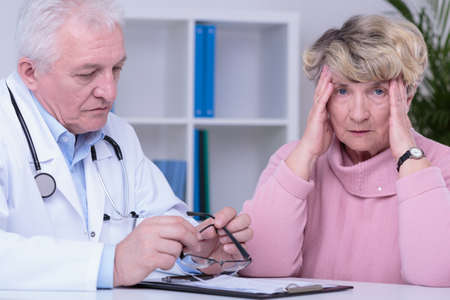 bad color: Older experienced physician with bad news and worried patient Stock Photo