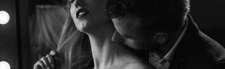 enamorados besandose: atmósfera entre mujer y hombre en el dormitorio Foto de archivo